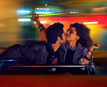 Maia und Raja küssen sich in einer Gondel sitzend. Der Hintergrund ist unscharf und bunt