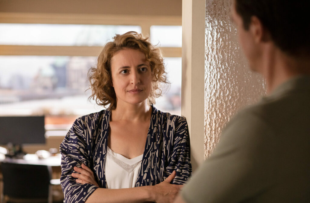 Maren Eggert lehnt mit verschränkten Armen gut gelaunt am Türrahmen und hört Dan Stevens zu - Ich bin Dein Mensch