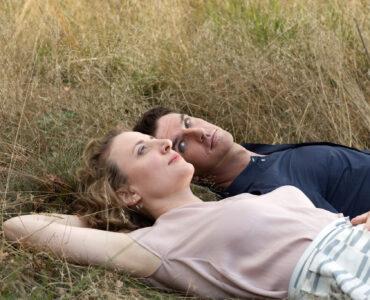 Maren Eggert und Dan Stevens relaxen verträumt auf der Wiese