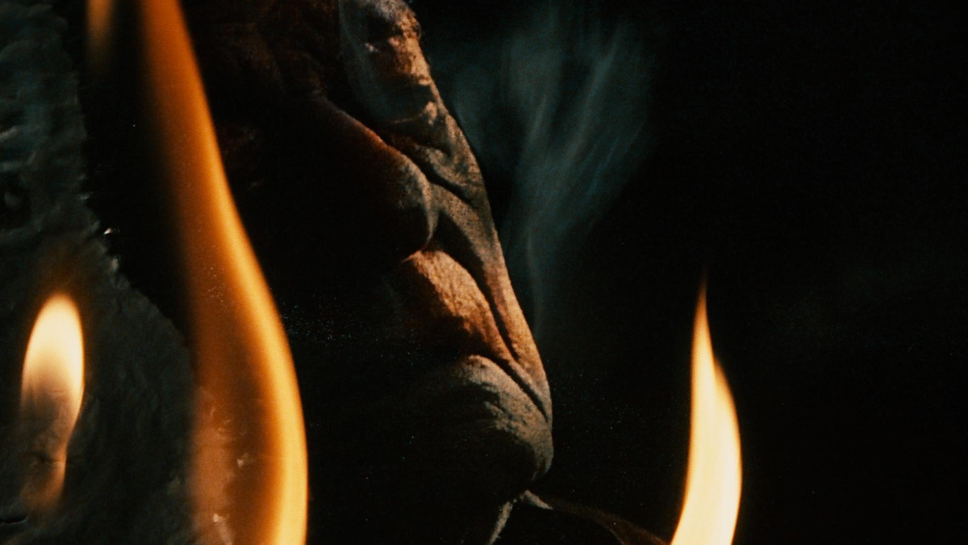 Man sieht eine Nahaufnahme es älteren Männergesichts. Insgesamt ist das Bild sehr düster und im Vordergrund sieht man drei Flammen zur Beleuchtung