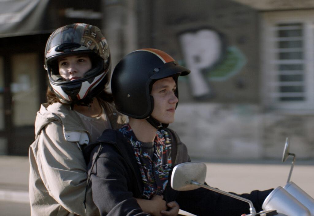 Faruk und Mona fahren mit dem Motorroller durch die Stadt - Tabija