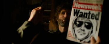 Sharlto Copley schaut in seinen Spiegel, um das eigene Gesicht mit dem Konterfei auf dem Fahndungsplakat zu vergleichen - Ted K