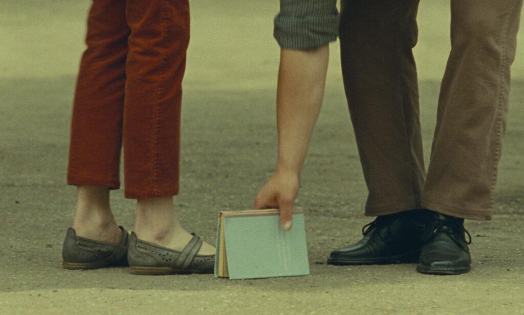Wir sehen nur die Beine von Lisa und Giorgi, er hebt gerade ein Buch auf, das ihr runtergefallen ist - Was sehen wir, wenn wir zum Himmel schauen?