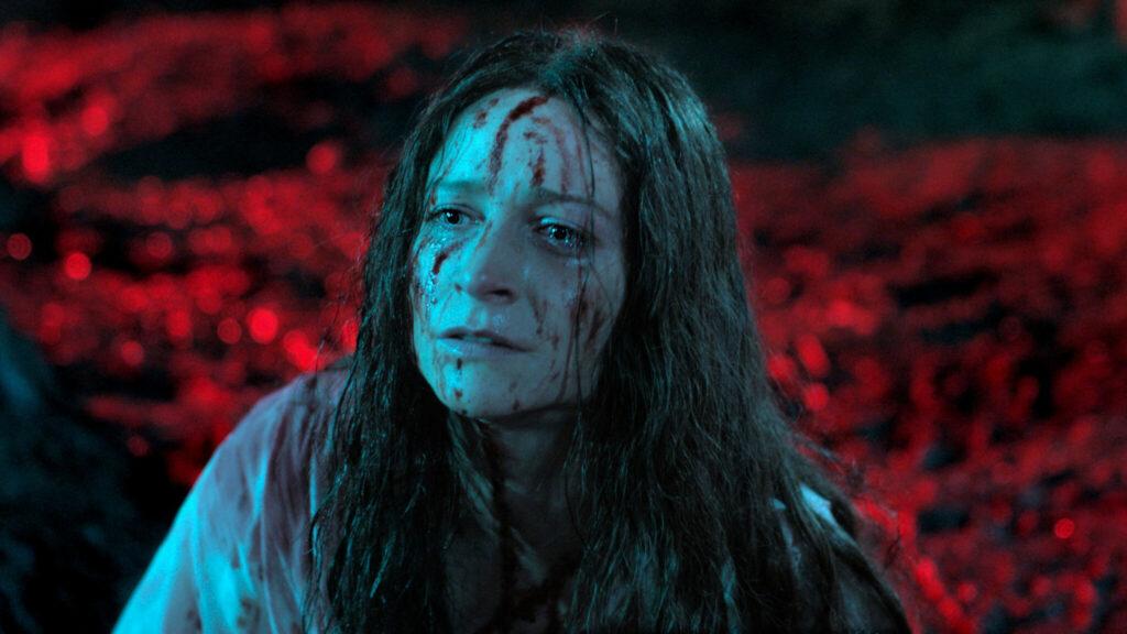 Niamh Algar scheint in Trance, ist in bläuliches Licht getüncht und mit Blut besudelt - Censor