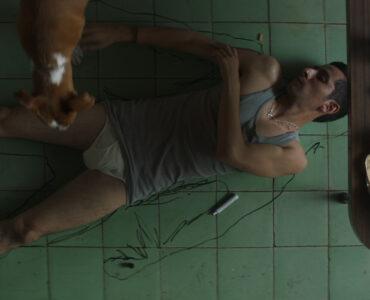 Montoya liegt auf dem Küchenboden und zeichnet seinen Körperumriss auf den Boden, während sein Hund zusieht - A Cop Movie