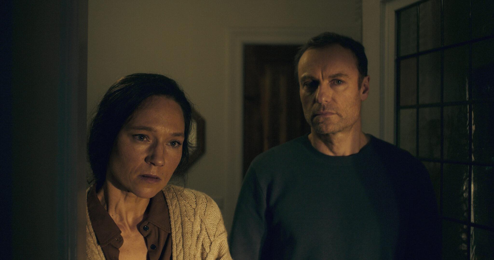 Nina (Sabine Timoteo) steht neben Jan (Mark Waschke) in einem verdunkelten Raum. Beide blicken nachdenklich in Richtung Betrachter.