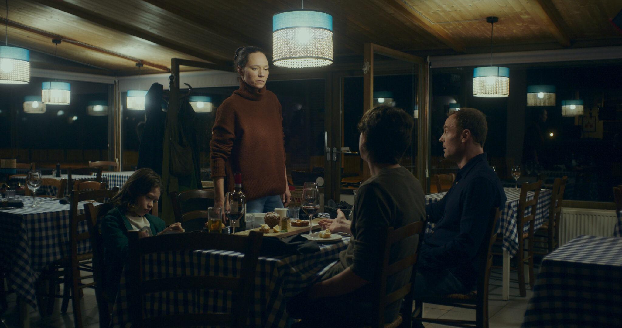 Die Familie von Nina (Sabine Timoteo) und Jan (Mark Waschke) an einem Tisch in einem Restaurant. Auf dem Tisch stehen einige Teller mit Speisen und Gläser mit Wein und andere Getränke. An der Decke sieht man blauweiße Deckenleuchten.