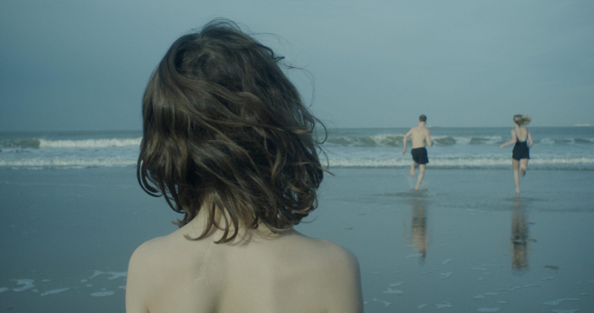 Von hinten sieht man Max (Wanja Kube) der am Strand steht und Richtung Wasser, wo seine Schwester und sein Vater hinrennen.