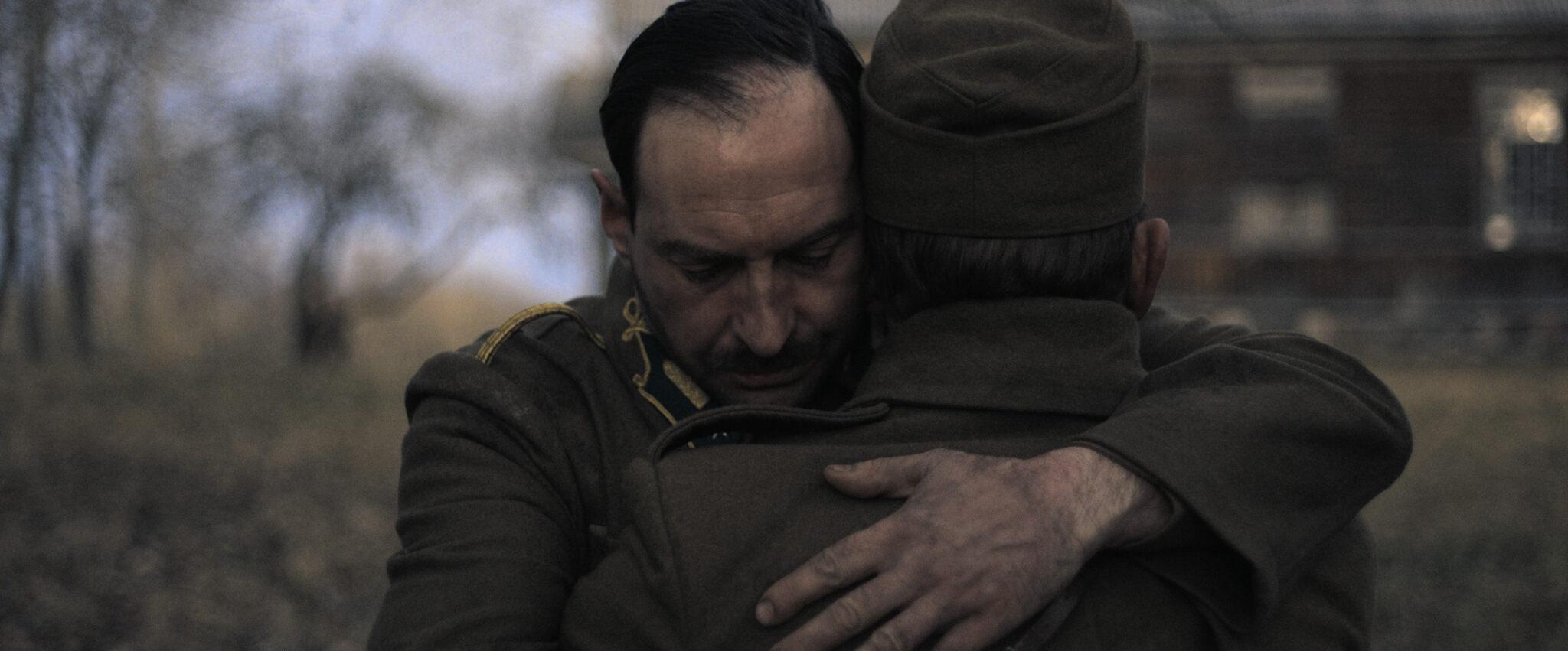 In Natural Light umarmen sich zwei uniformierte Soldaten. Einen mit Kappe sieht man nur in der Rückansicht, den anderen mit geschlossenen Augen von vorn.