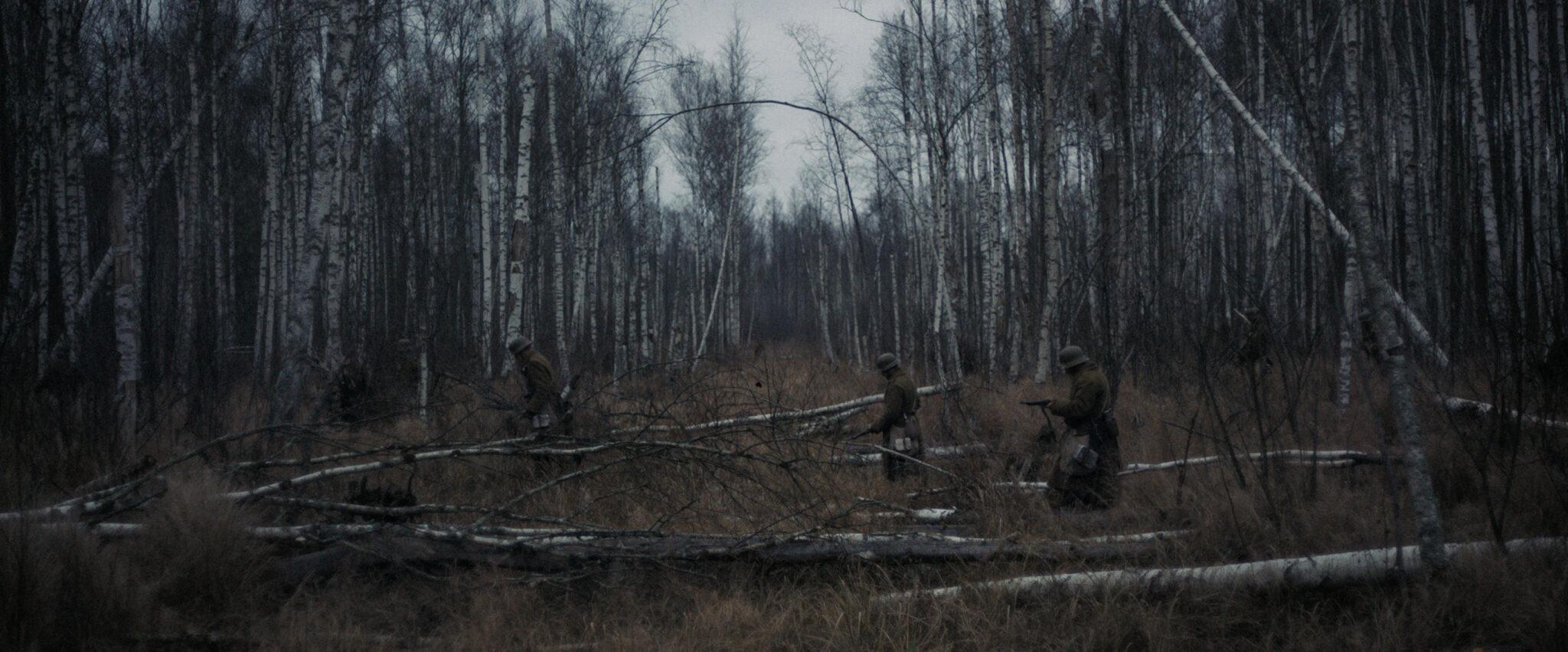 Eine Totale zeigt eine Waldszene, in der drei uniformierte Soldaten von rechts nach links eine Lichtung durchschreiten. Im Hintergrund sieht man etliche karge Birkenstämme.