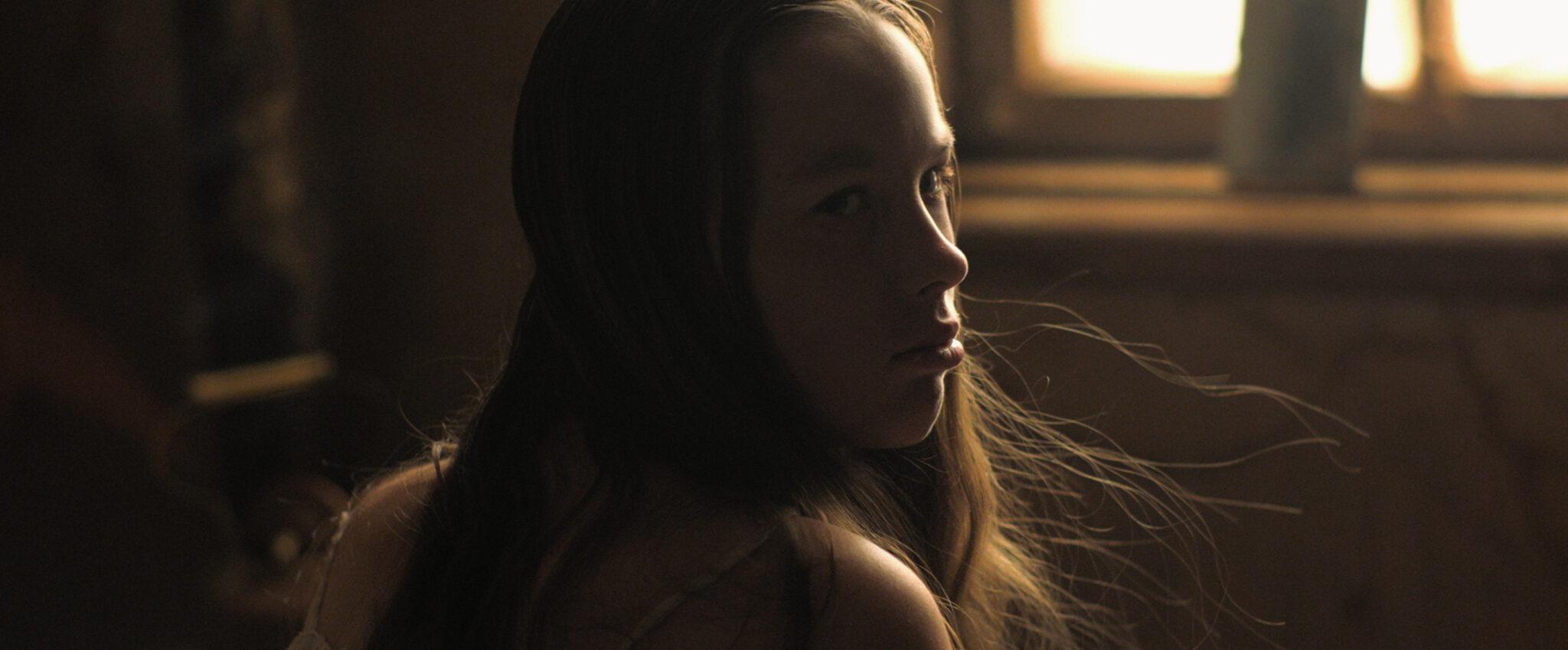 Ein junges Mädchen im Profil. Sie sieht traurig aus, einige Haare wehen vor ihr in die Luft.