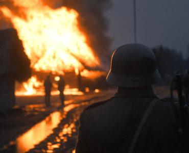 Man sieht einen Soldaten von hinten, der ein niederbrennendes Gebäude aus sicherer Entfernung ansieht.