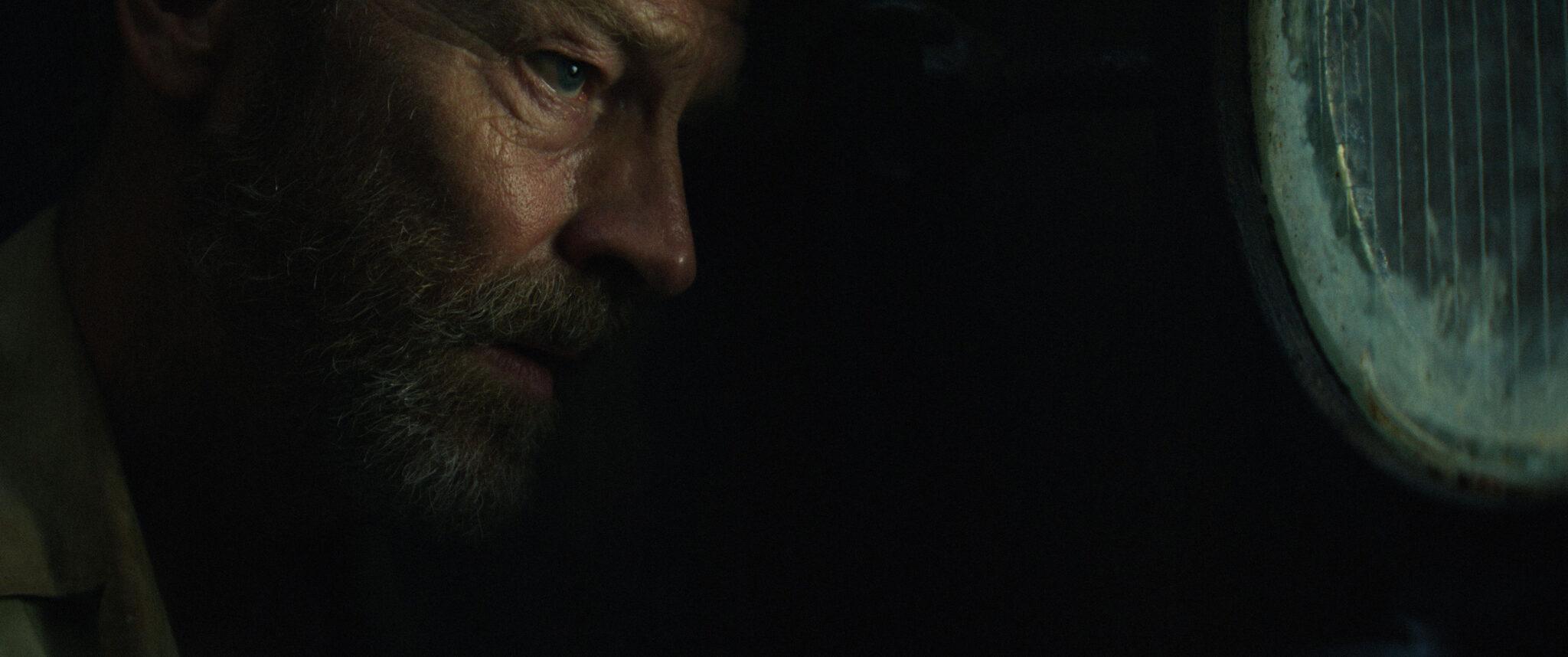 Gibson (Iain Glen) blickt in Tides ernst durch ein rundes Fenster. Der Großteil des Bildes ist im Dunkeln.