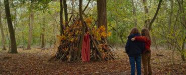 Die beiden Mädchen stehen Arm in Arm vor ihrer selbst gebauten Hütte im Wald - Petite maman