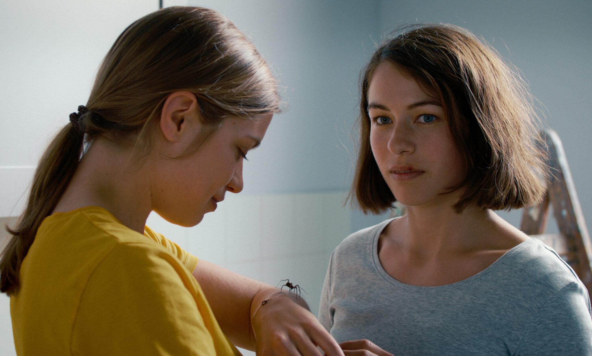 Das linke Mädchen in gelbem T-Shirt hält eine Spinne auf der Hand, das rechte Mädchen (Henriette Confurius) trägt ein graues Shirt und blickt apathisch in den Raum.