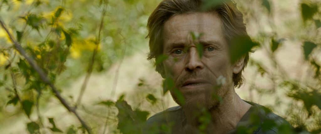 Willem Dafoe in Siberia als Clint in freier Natur, umgeben von blühenden Pflanzen.