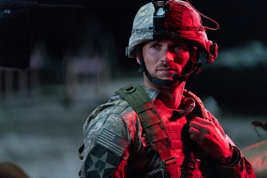 Clint Romesha (Scott Eastwood) steht mit Kampfanzug und Helm im roten Licht.