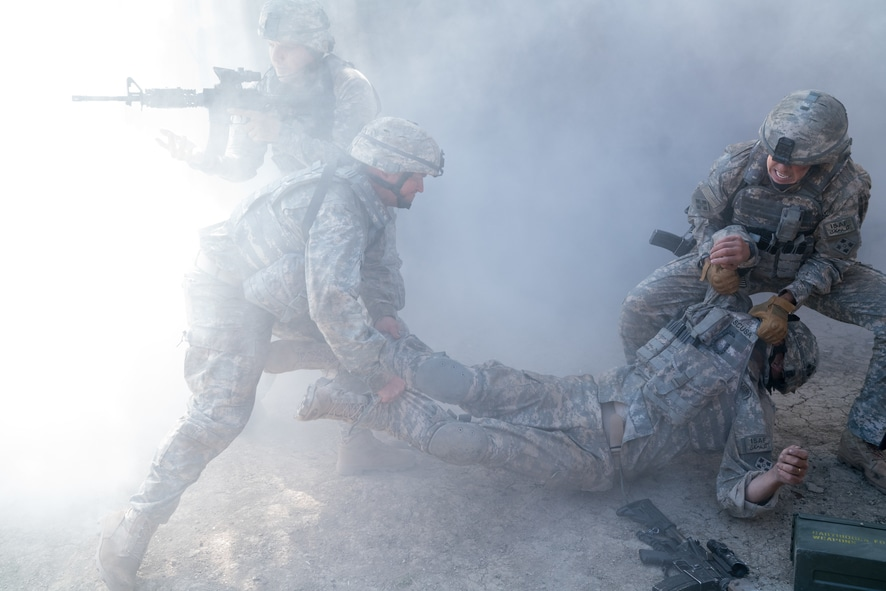 Vier Soldaten befinden sich in einer Staubwolke. Zwei von ihnen tragen einen verletzten Kameraden, ein weiterer im Hintergrund zielt mit dem Gewehr, um die Kollegen zu sichern in The Outpost - Überleben ist alles.