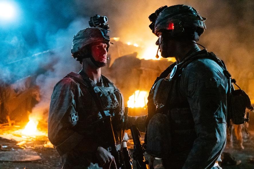 Zwei Soldaten unterhalten sich in The Outpost - Überleben ist alles. Beide tragen volle Kampfmontur mit Helm. Im Hintergrund brennt ein Gebäude