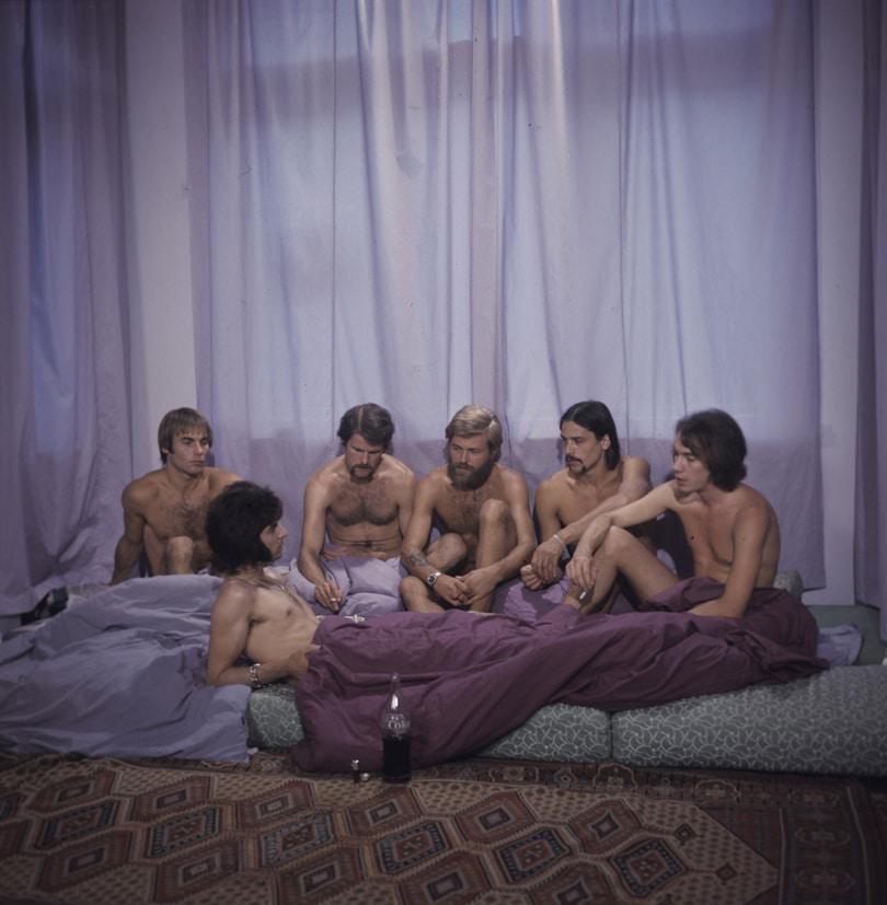 Sechs nackte Männer befinden sich in einem Zimmer mit violetten Gardinen. Einer liegt, die anderen sitzen. Nicht der Homosexuelle ist pervers, sondern die Situation, in der er lebt, ist eine wichtige Station für die LGBTQ+ Repräsentation in Filmen