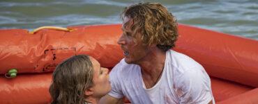 Charlie (Aaron Jakubenko) nimmt Kaz (Katrina Bowden) in auf dem Rettungsboot in den Arm, um sie vor dem gefährlichen Hai zu schützen.
