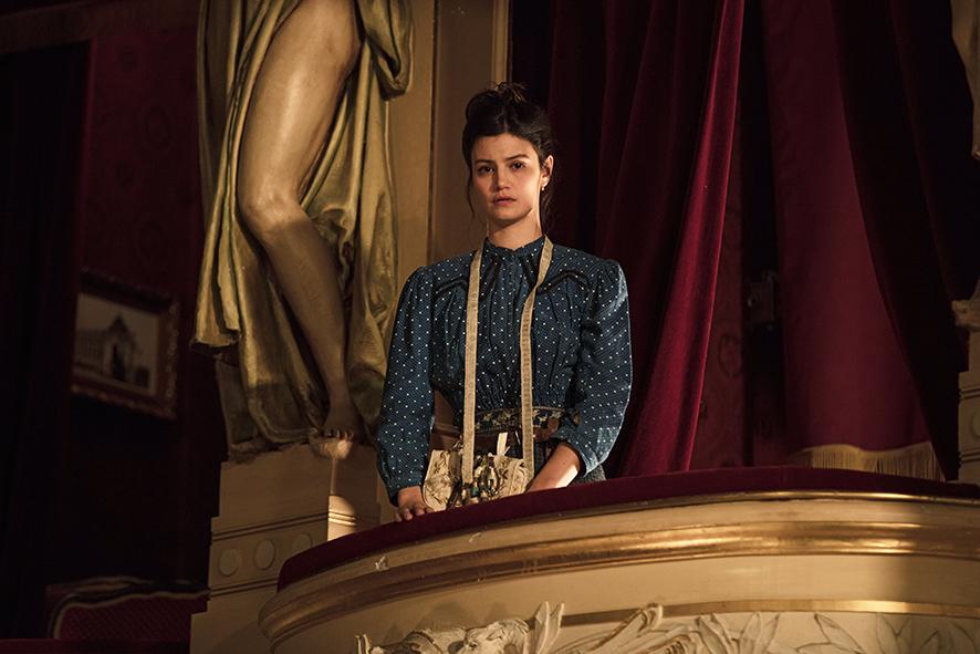 Schneiderin Jeanne blickt vom Balkon gebannt auf die Proben zu Cyrano de Bergerac.