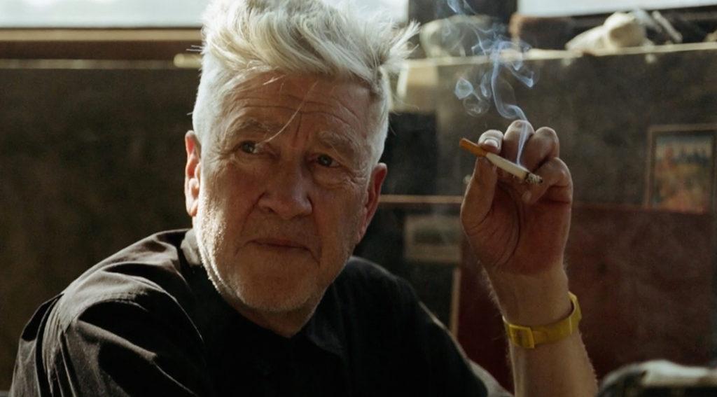 David Lynch sitzt in schlichtem T-Shirt und Zigarette in der Hand in seinem Zimmer