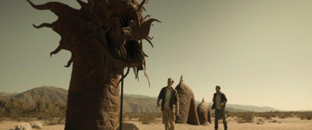 Aaron und Justin laufen durch die Wüste. Neben ihnen ist eine große Drachen-Statue