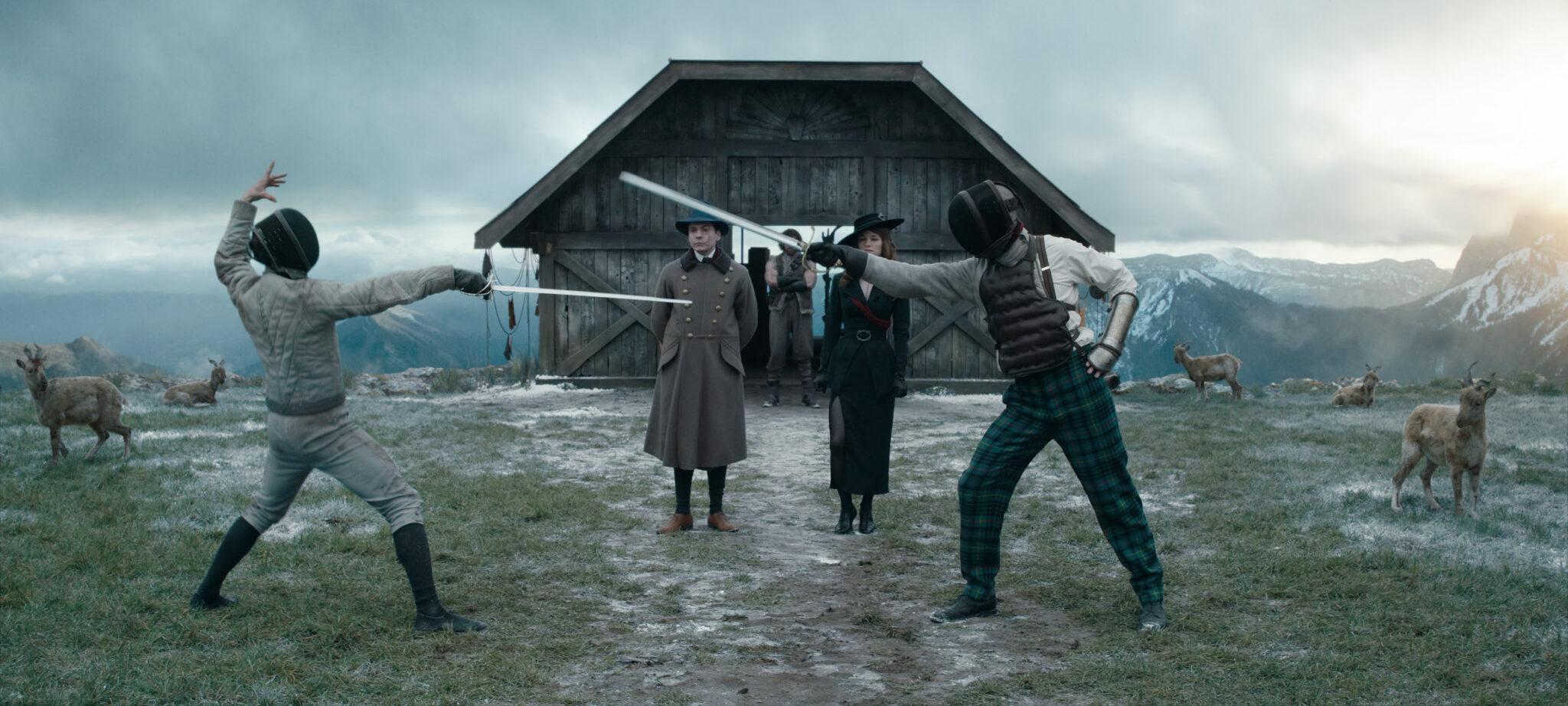 Erik (Daniel Brühl) und Mata Hari (Valerie Pachner) stehen vor einer Scheune in der Wildnis und sehen einen Fechtkampf zwischen zwei maskierten Duellanten an.