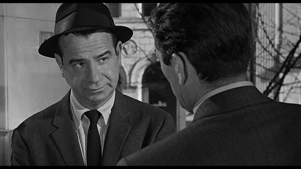 Detektiv Caselle (Walter Matthau) schaut in Die 27. Etage Stillwell (Gregory Peck) fragend an, den Hut an der Stirn hochgeschoben.