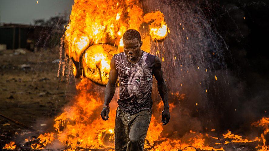 Junger Mann vor einem lodernden Feuer, Welcome to Sodom