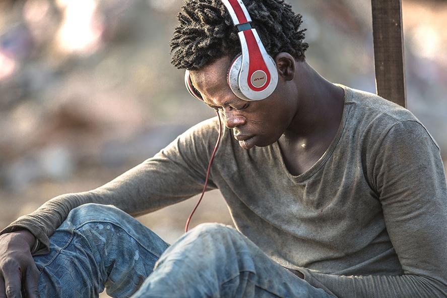 Junger Mann mit Kopfhörern sitzt auf der Müllhalde