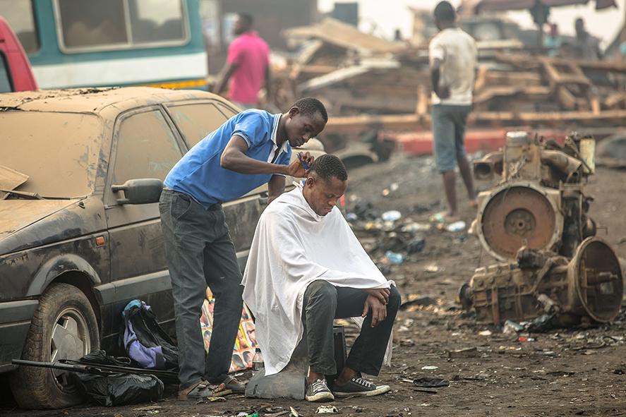 Einem Mann werden inmitten der Müllhalde die Haare geschnitten, Welcome to Sodom - Dein Smartphone ist schon hier