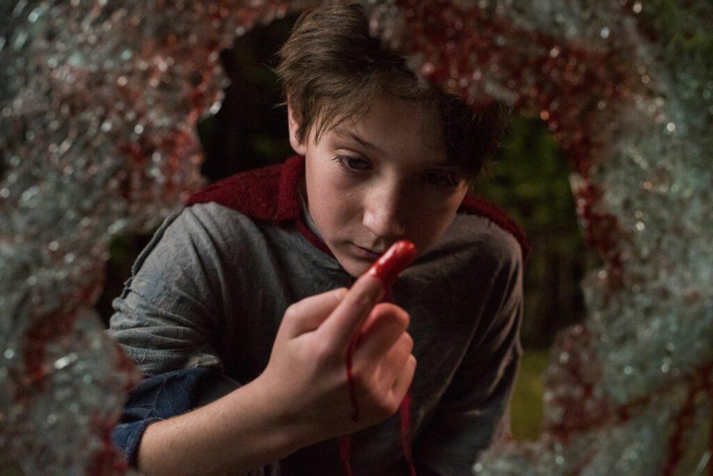 Brandon sieht sich seine blutbefleckten Finger an