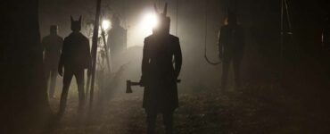 Um einer Schaukel herum sind die maskierten Sektenmitglieder samt Waffe zu sehen. Im Bildhintergrund erstrahlen Scheinwerfer die Nachtszene