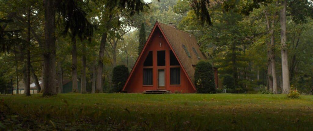 Ein rotes Landhaus mit großen Fenstern zwischen Bäumen und Wiesen in 30 Miles From Nowhere
