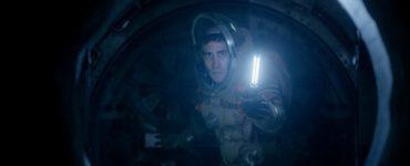 Jack Gyllenhal trägt einen offenen Raumanzug und erhellt mit einem Leuchtstab das innere einer Fluchtkapsel
