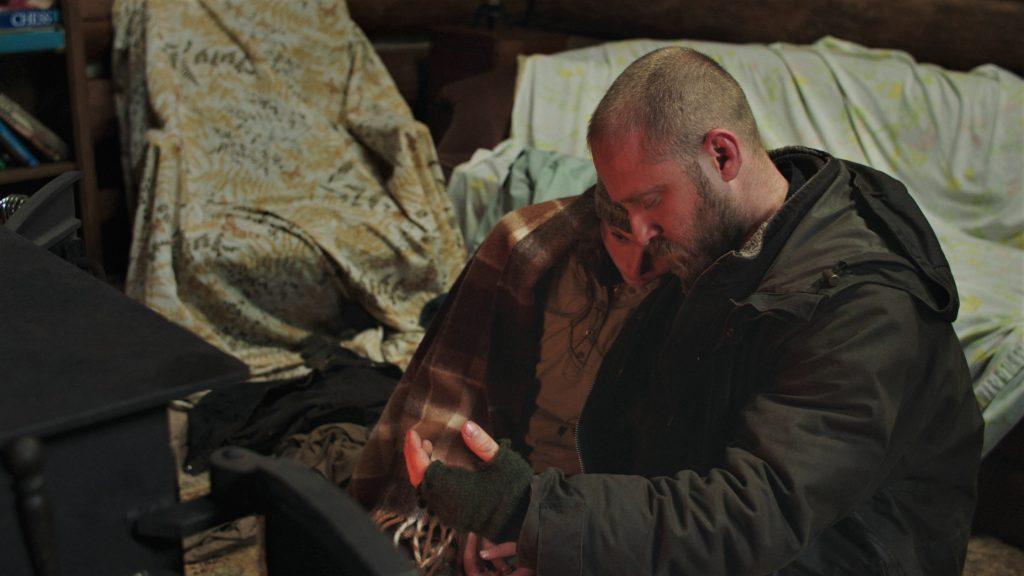 Durchgefroren und erschöpft von ihrer beschwerlichen Reise wärmen sich Tom und Will in Leave No Trace vor dem Kamin. © 2018 My Abandonment, LLC. All Rights Reserved.