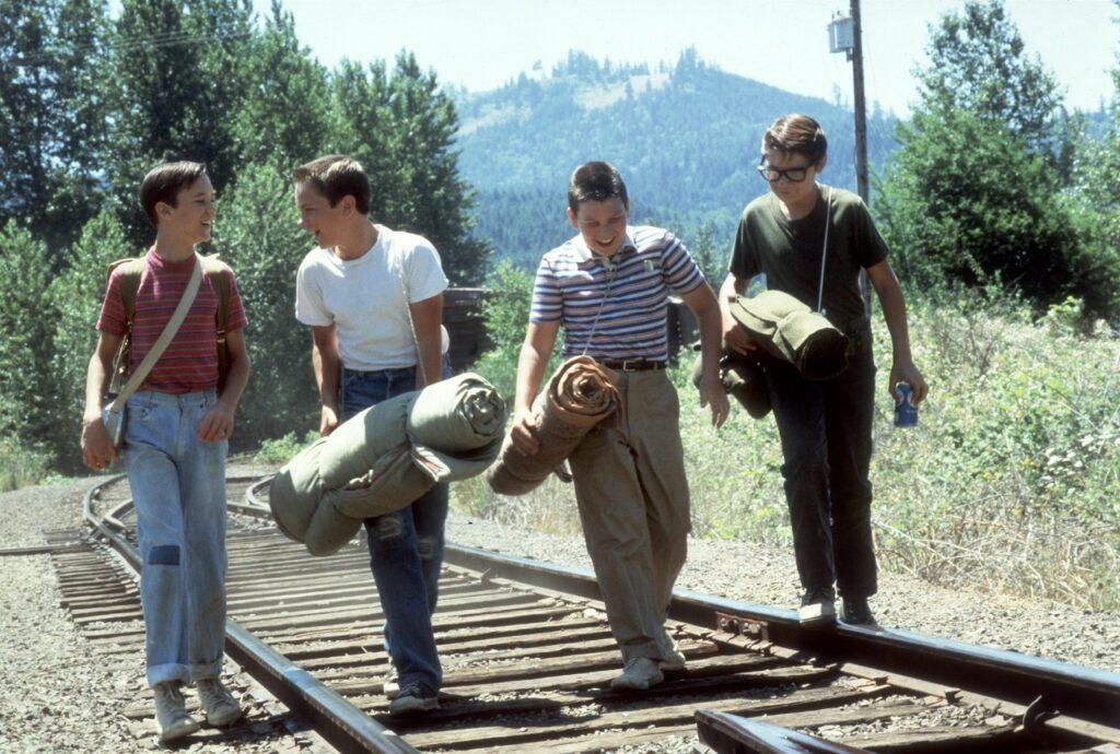 Die vier Jungen schlendern mit Schlafsäcken bepackt über ein Bahngleis, in Erwartung eines großen Abenteuers in Stand by Me - Die 10 besten Stephen King Verfilmungen