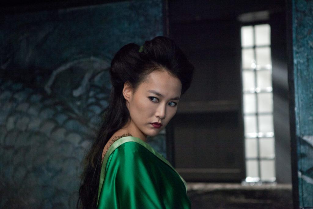 Die Hexe Mizuki guckt mit heimtückischen Blick über ihre Schulter. Sie trägt ein grünes Seiden-Gewand und langes, schwarzes Haar.