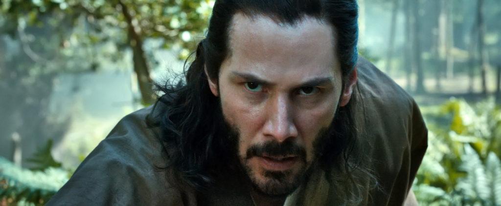 Kai (Keanu Reeves) visiert in 47 Ronin mit konzentrierten Blick ein Ziel außerhalb des Bildbereichs an. Es handelt sich um eine Großaufnahme von Reeves Gesicht, im Hintergrund ist unscharf ein Wald zu erkennen.