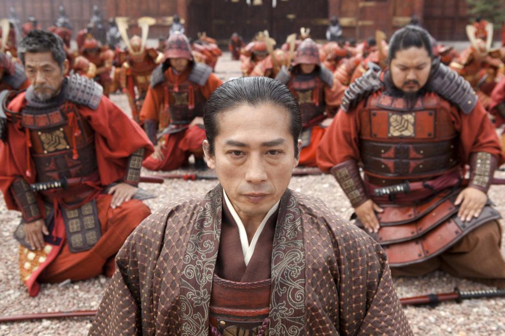 Hiroyuki Sanada kniet als Ôishi in 47 Ronin zusammen mit den anderen Samurai auf steinigem Boden. Allesamt tragen sie rotfarbene Samurai-Rüstungen und sehen andächtig Richtung Boden.