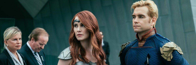 Queen Maeve und Homelander (Anthony Starr) stehen in ihrem Heldenoutfit vor einem fensterlosen Gebäude. Außerdem sieht man drei Personen in Anzügen im Hintergrund.