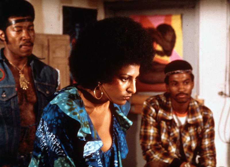 Foxy konzentriert sich auf Etwas außerhalb des Bildausschnitts, im Hintergrund sind Mitglieder einer Straßengang.