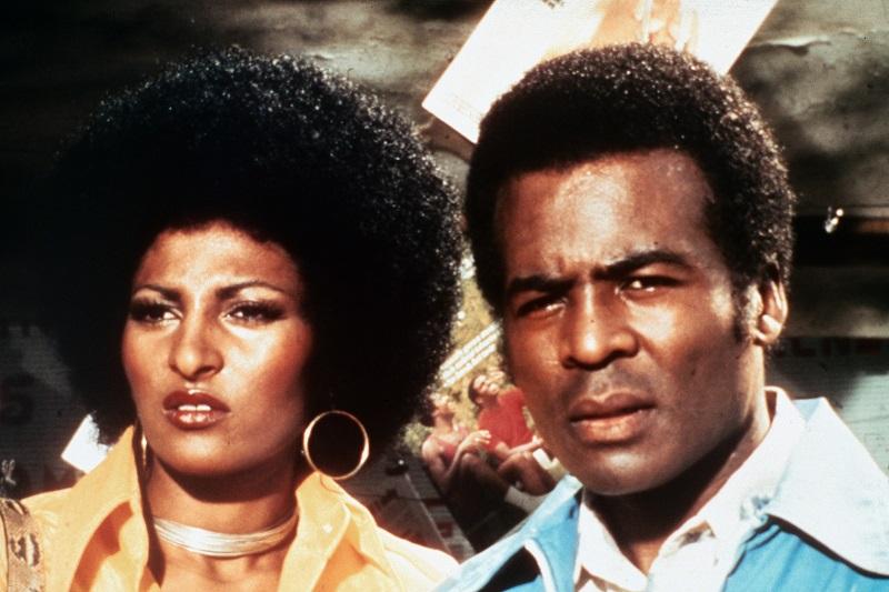 Foxy Brown mit Afro-Frisur und großem Ohrring neben ihrem Freund Michael, beide schauen etwas ratlos drein.