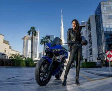 Eine junge, chinesische Frau in Leder-Kluft posiert neben ihrem Motorrad - Neu auf Sky im August 2021