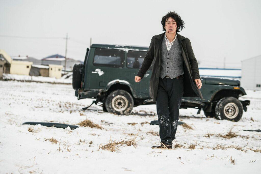 Byung-Su steht in Memoir of a Murderer verletzt auf einem verschneiten Feld, hinter ihm steht sein Auto