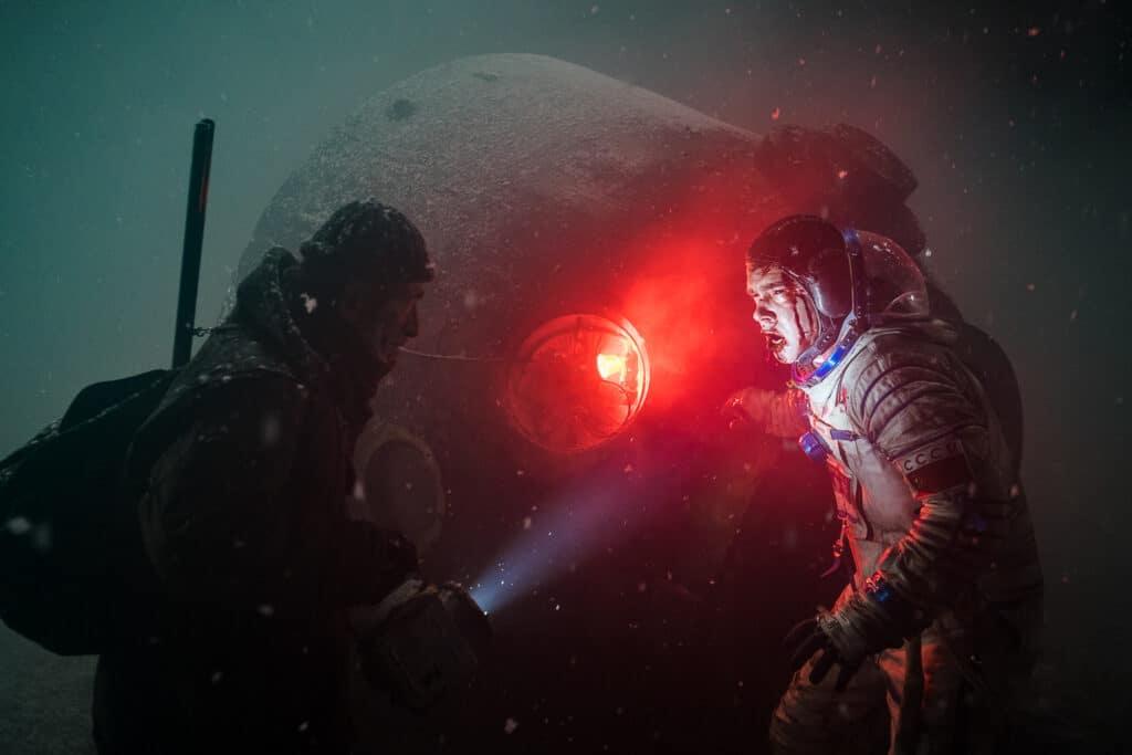 Ein Kosmonaut steht vor einer Raumkapsel und wird von einem Mann mit Taschenlampe angestrahlt