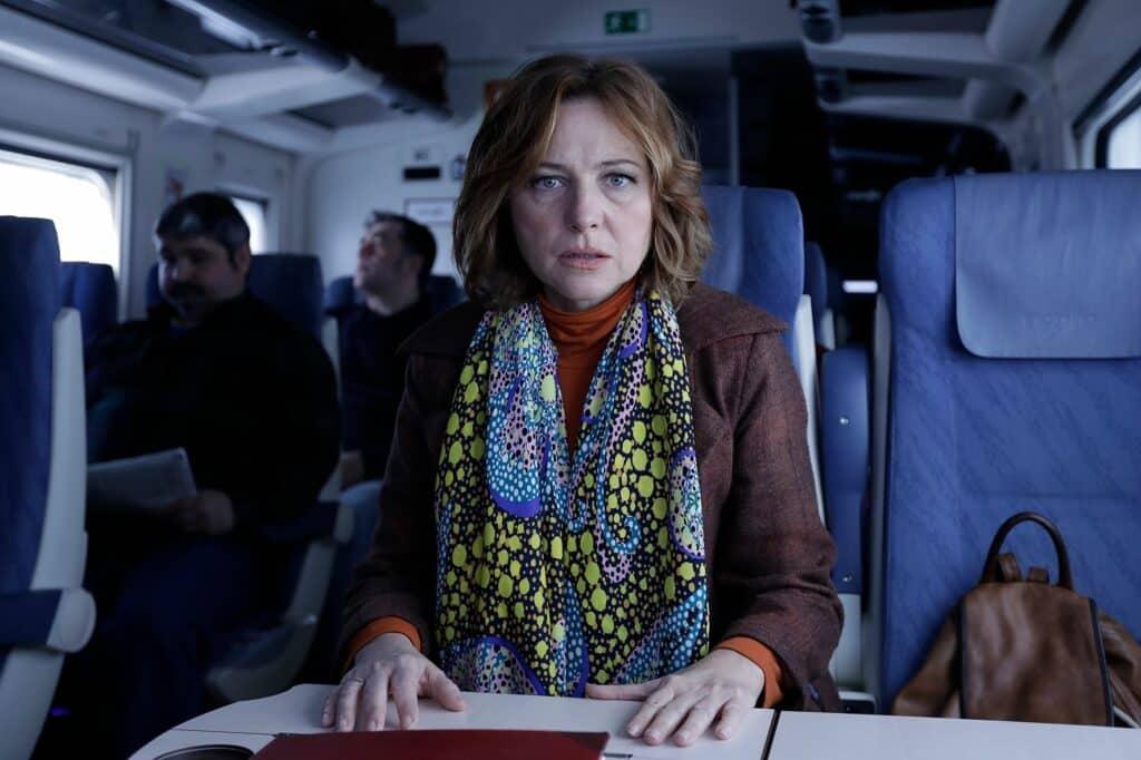 Helga sitzt in einem Zug und schaut verstört in die Kamera