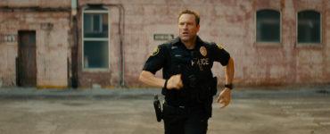 Frank Penny (Aaron Eckhart) läuft über eine Straße. Sein Gesicht ist sehr fokussiert.